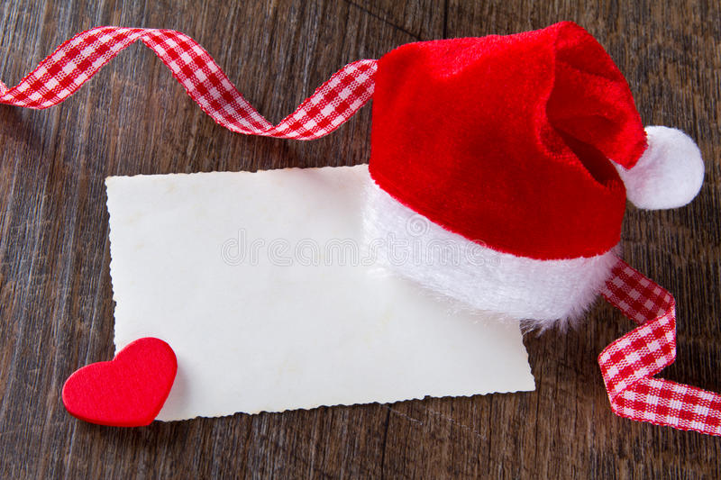 Father Christmas hat card heart. Father Christmas cap with yellowed card, red heart and checkered ribbon on dark wood, copy space stock photo