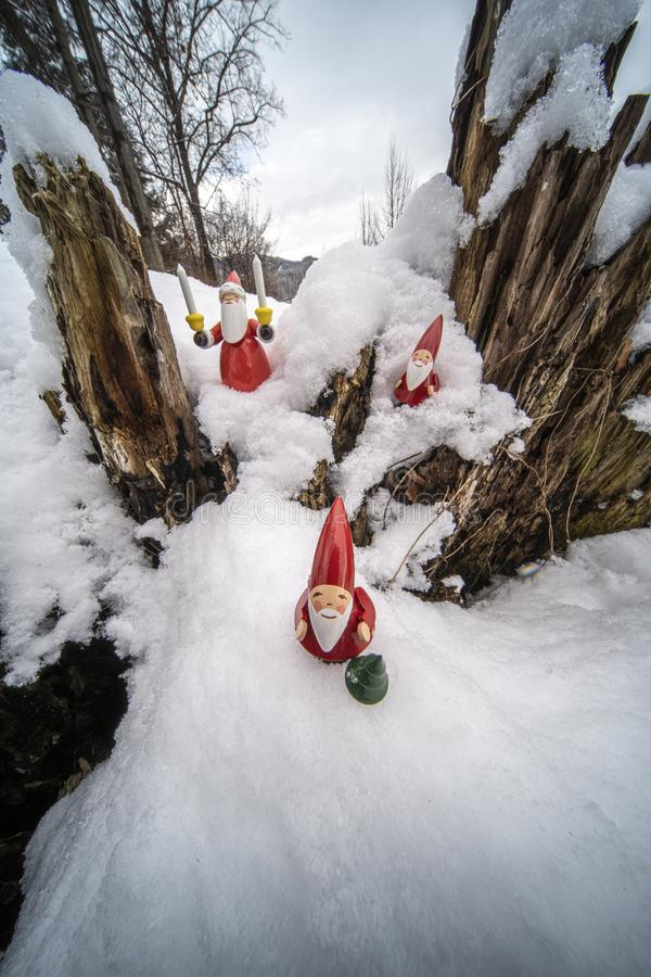Christmas ornaments in snow. Father Christmas and his helpers outdoors in the snow with tree backdrop setting the mood for Christmas royalty free stock photography