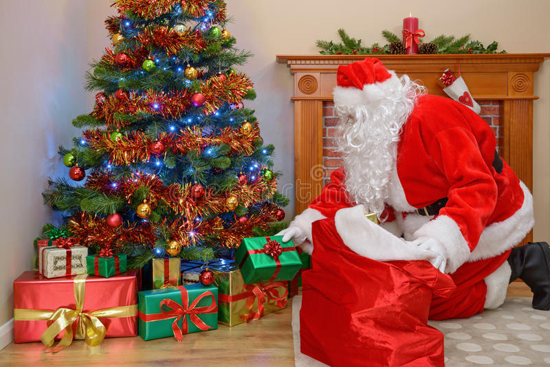 Father Christmas putting gifts under the tree royalty free stock photos