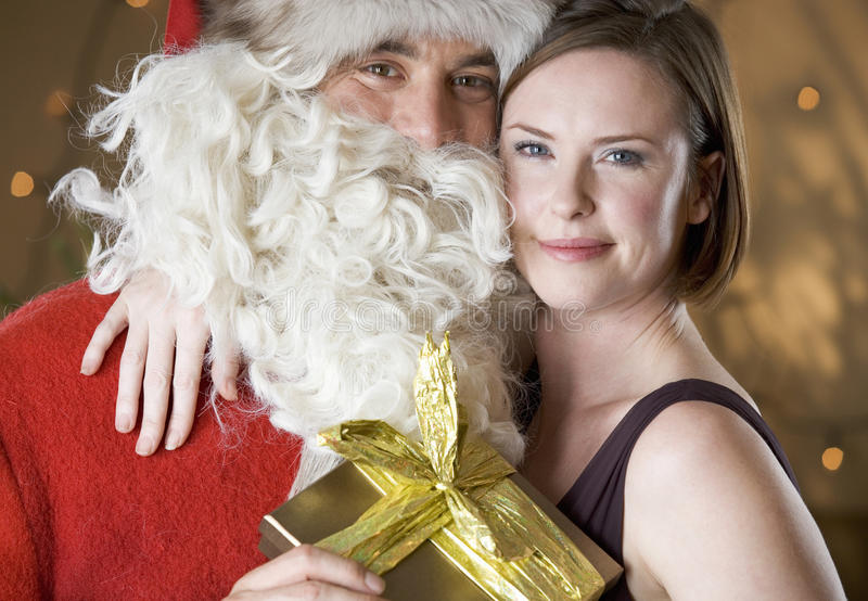 Father Christmas/Santa Claus giving a present to a mother stock images