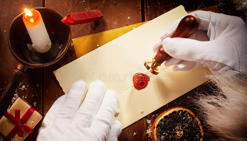 Father Christmas sealing a Christmas letter with a vintage seal and red wax showing his face in a view from above in an olden day royalty free stock photography