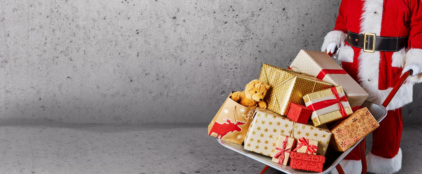 Father Christmas with a wheelbarrow full of colorful wrapped Xmas gifts in a panorama banner over grey concrete wall with copy. Space stock images