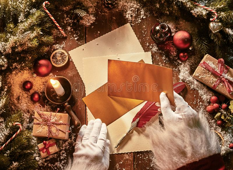 Father Christmas writing a letter to celebrate Xmas in an overhead view of his hands holding envelopes above vintage paper and a stock photos