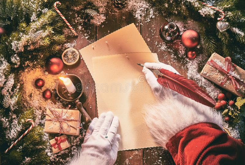 Father Christmas writing a seasonal letter using a vintage feather quill pen on old yellowed paper surrounded by Xmas decorations stock photo