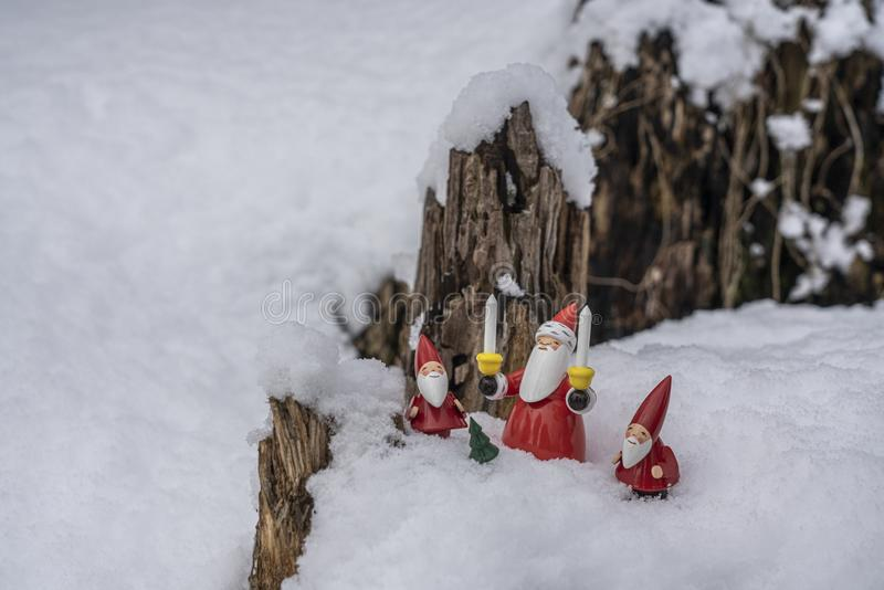 Christmas ornaments in snow. Father Chritsmas and his helpers outdoors in the snow with tree backdrop setting the mood for Christmas royalty free stock image
