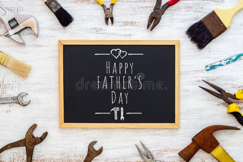 Father' ; concept de fond de jour de s Vieux outils de bricolage rouillés avec le tableau noir et le texte écrivant Father&#x images libres de droits