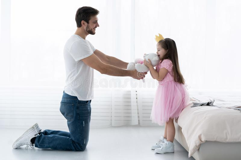 Father Congratulates Daughter with Happy Day 8 March. Daughter and Father Smile. Big Bear for Beautiful Daughter. Happiness and Springtime for Happy Daugter stock photo