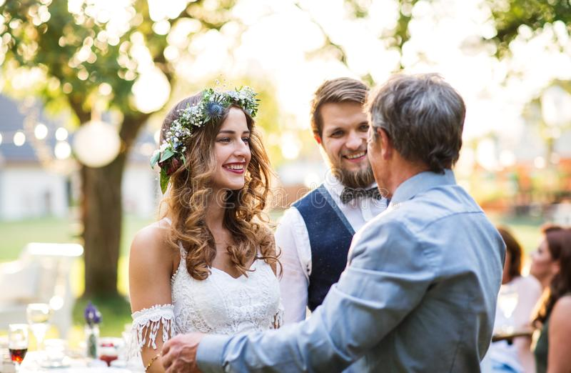 A father congratulating bride and groom at wedding reception in the backyard. stock image