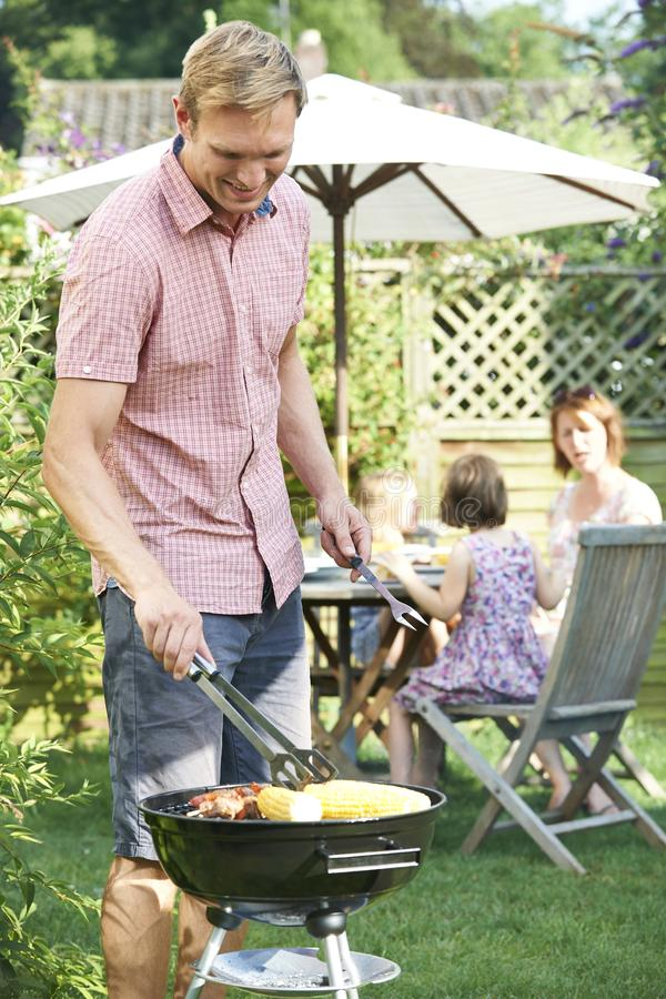 Father Cooking Barbeque For Family In Garden At Home stock photo