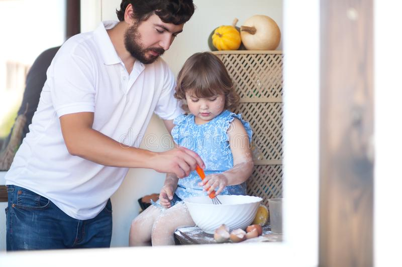 Father cooking cake with his cute little daughter stock photos