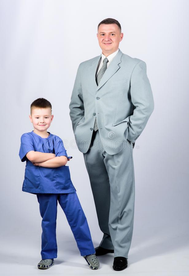 Father and cute small son. Child care development upbringing. Respectable profession. Man respectable businessman and. Little kid doctor uniform. Family stock images