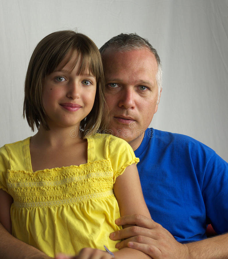 Father and daughter. Blue and yellow shirt and dress grayish background stock photography