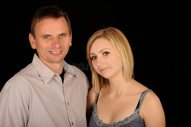 Father and daughter. A studio portrait of a father and teenage daughter. Black background royalty free stock photos