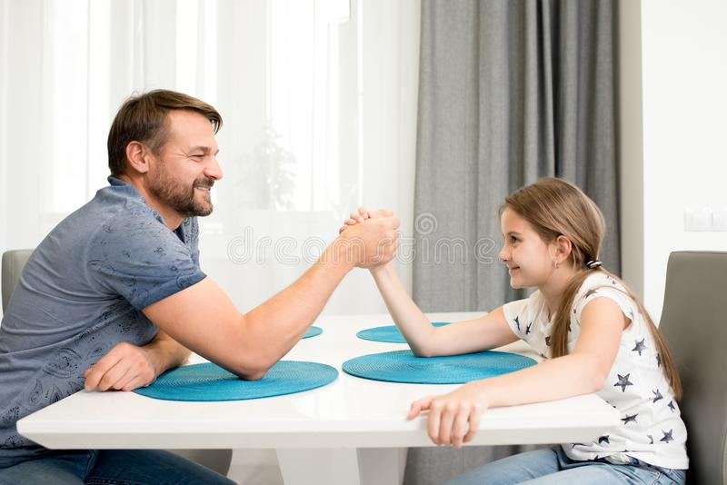 Father and Daughter Armwrestling. Side view portrait of bearded father armwrestling with teenage daughter at kitchen table smiling happily royalty free stock image