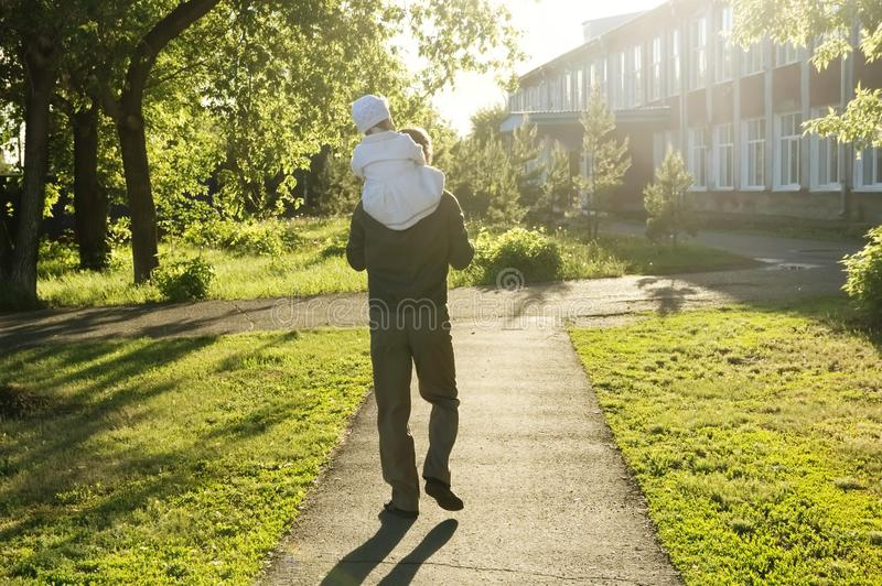 Father with daughter baby on shoulders walking away in park at sunny day. Family authentic lifestyle stock images