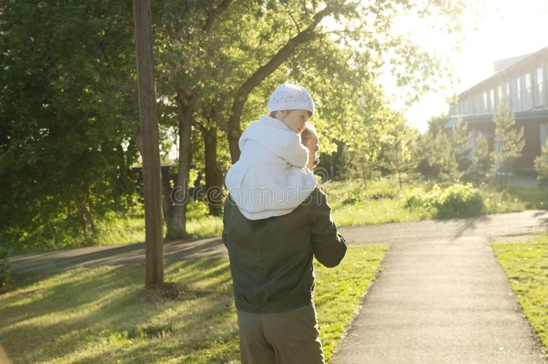 Father with daughter baby on shoulders walking away in park at sunny day. Family lifestyle portrait royalty free stock images