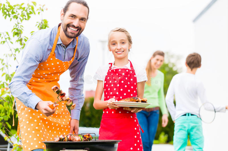 Father and daughter barbecue together. Father and daughter barbecue meat spits and sausages at family garden BBQ stock photo