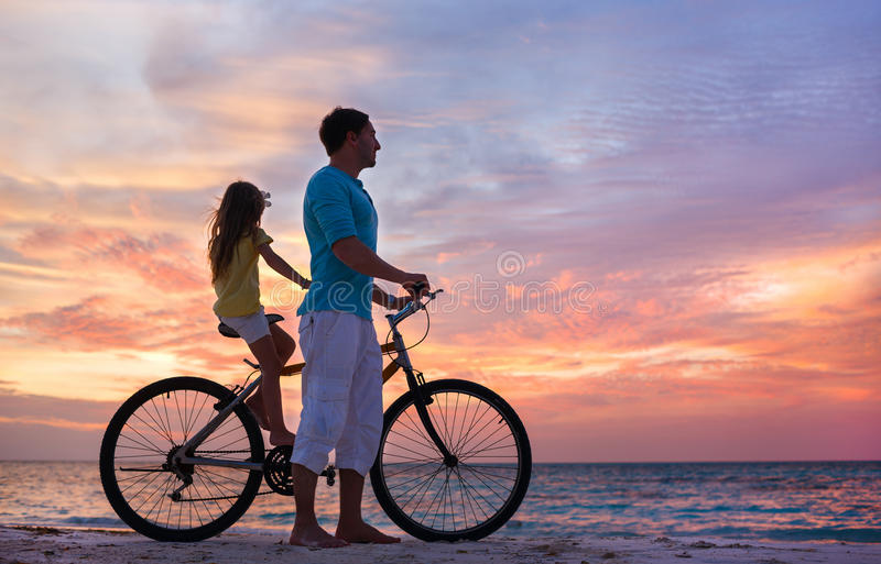 Father and daughter on a bike. Father and daughter with bike on a beach at sunset stock images