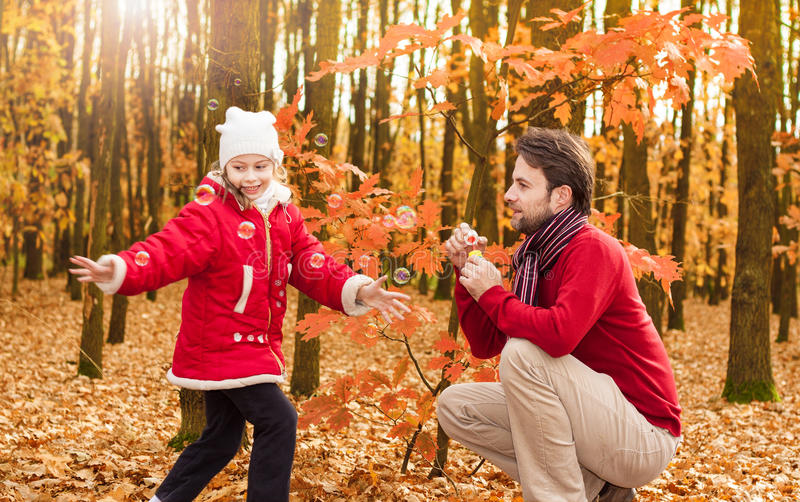 Father and daughter blowing bubbles outdoor in an autumn park stock images