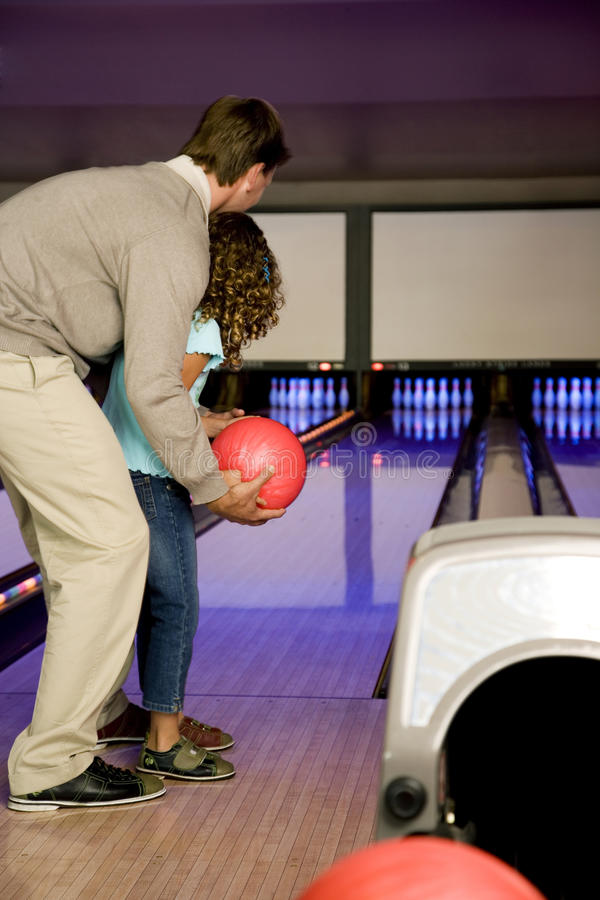 Father and daughter in a bowling alley, about to roll the ball stock images