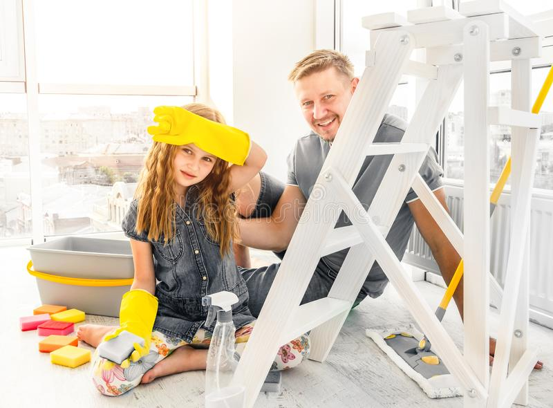 Father and daughter on break from cleaning royalty free stock image