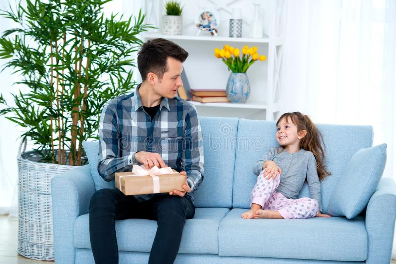 Father and daughter or brother and sister with a gift in the interior of the room. Father`s day holiday concept, Children`s Day.  royalty free stock photography