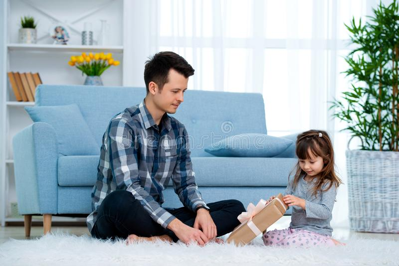 Father and daughter or brother and sister with a gift in the interior of the room. Father`s day holiday concept, Children`s Day.  royalty free stock photos