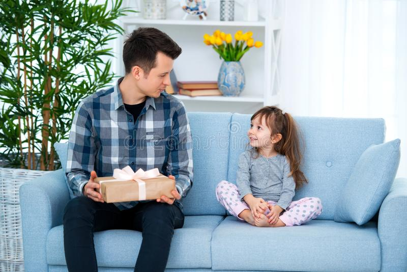 Father and daughter or brother and sister with a gift in the interior of the room. Father`s day holiday concept, Children`s Day.  stock photos