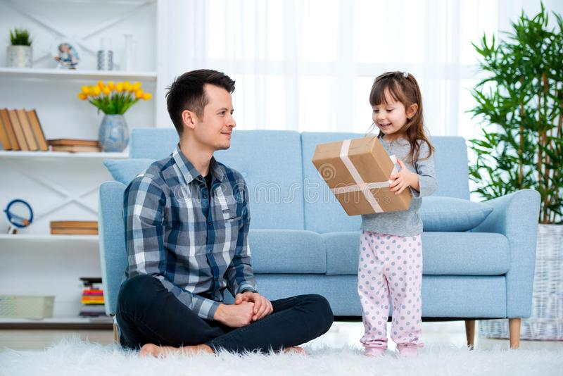 Father and daughter or brother and sister with a gift in the interior of the room. Father`s day holiday concept, Children`s Day.  royalty free stock photo