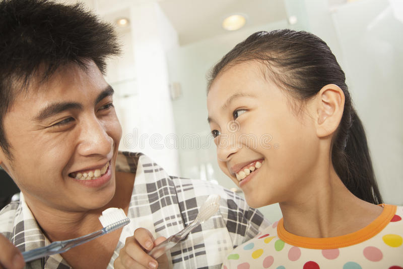 Father and Daughter Brushing Teeth Together stock photo