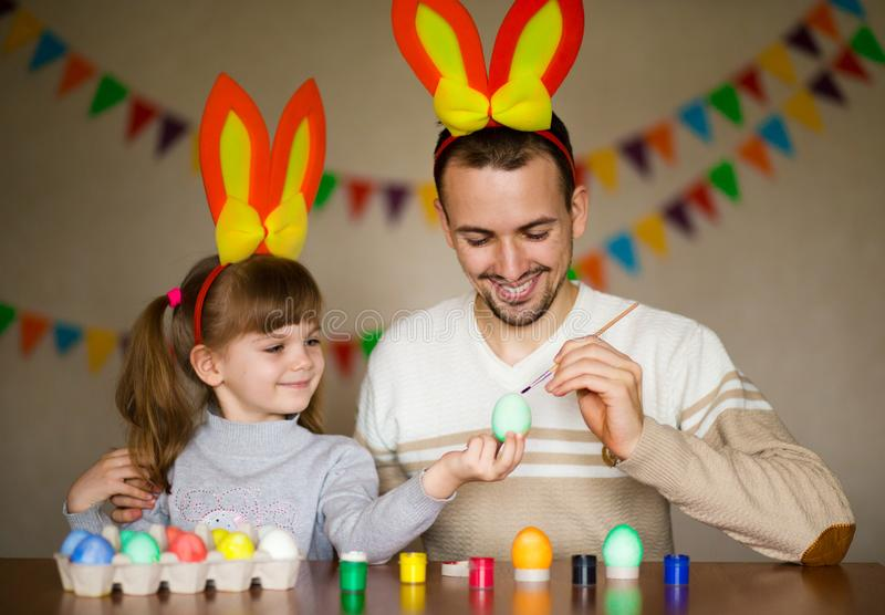 Father and daughter in bunny ears with colorful eggs in busket. Easter day. Modern Family preparing for Easter. royalty free stock photography