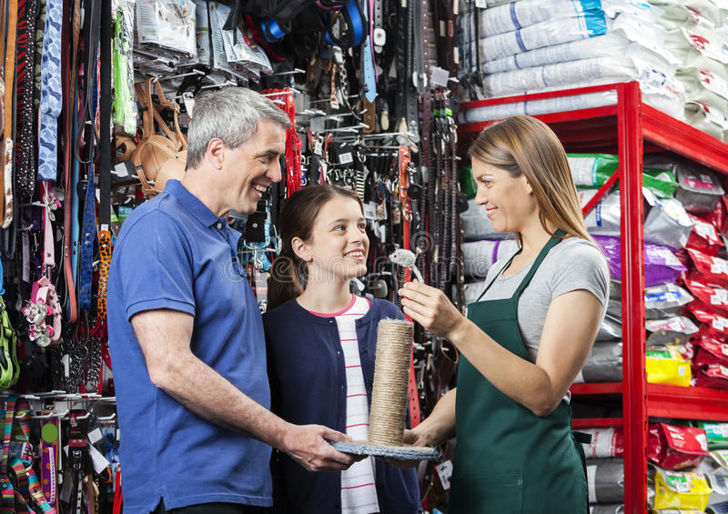 Father And Daughter Buying Cat Scratcher From Saleswoman royalty free stock photos
