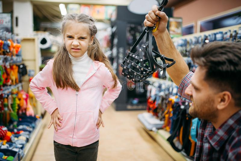 Father and daughter buying muzzle in pet shop. Father and little daughter buying muzzle in pet shop. Family chooses accessories for dog in petshop royalty free stock images