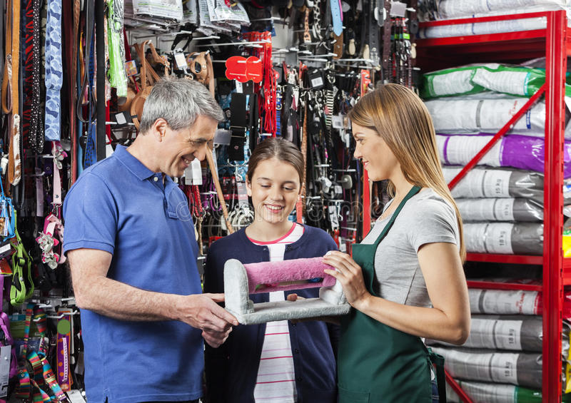 Father And Daughter Buying Pet Cat Scratcher From Saleswoman royalty free stock photography