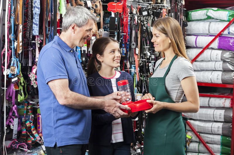Father And Daughter Buying Pet Food Bowl From Saleswoman royalty free stock image