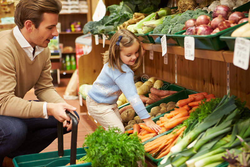 Father And Daughter Choosing Fresh Vegetables In Farm Shop. Young Father And Daughter Choosing Fresh Vegetables In Farm Shop stock photos