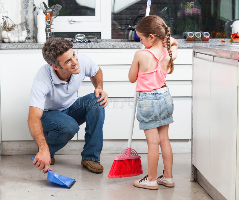 Father and daughter cleaning in the kitchen stock photos