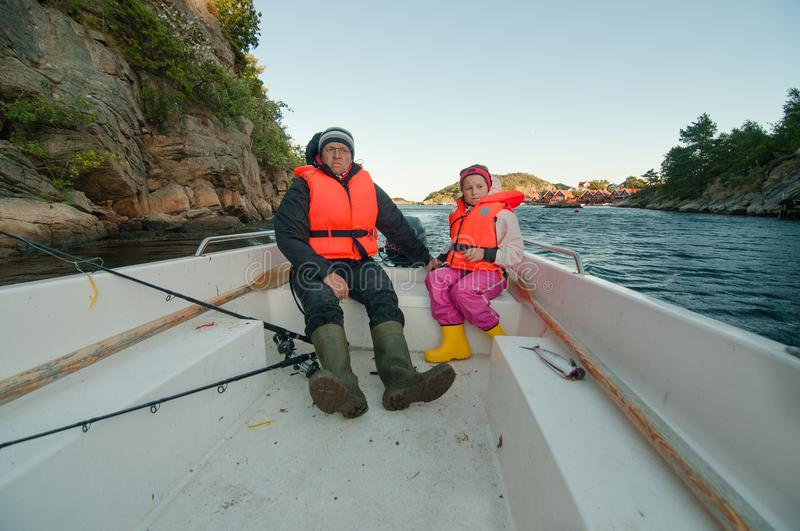 Father and daughter coming back from shining tour. In a motor boat with a catch royalty free stock photography