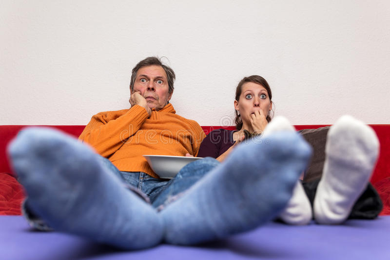 Father and daughter on a couch. Watching a scary movie royalty free stock image