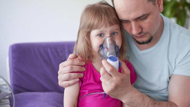 Father and daughter do inhalations. caring dad helps her daughter breathe through the mask. Treatment of respiratory tract stock photos