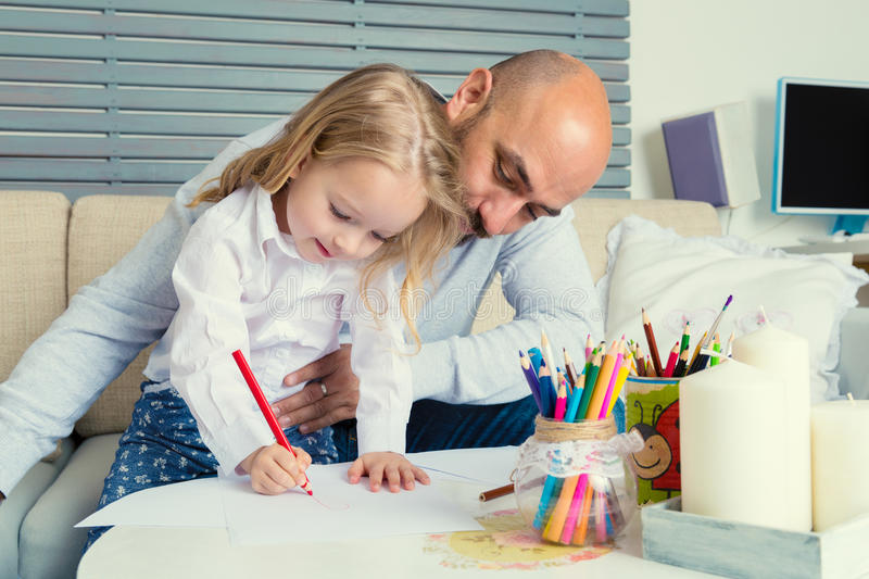 Father and daughter drawing together stock image