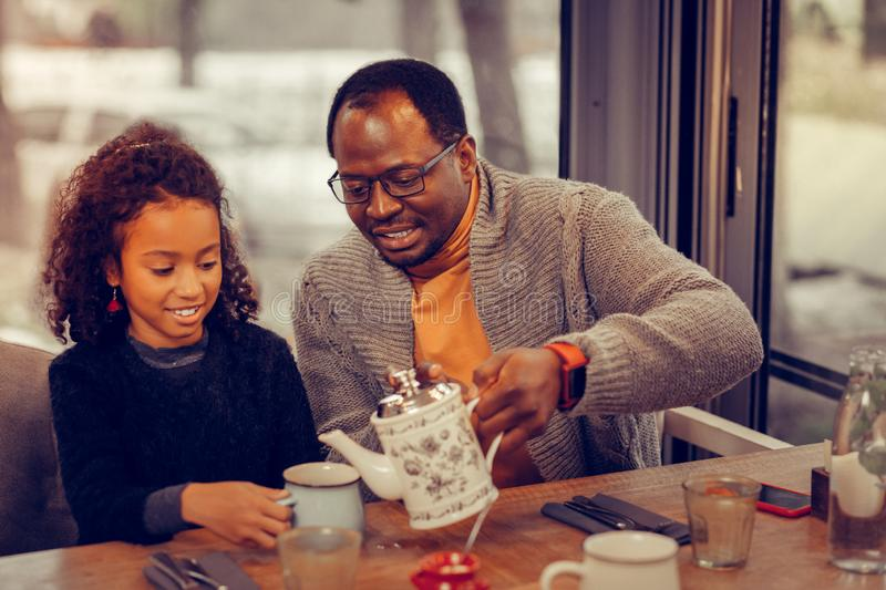 Father and daughter drinking tasty tea in cafeteria together. Tea in cafeteria. Loving father and cute little daughter drinking tasty tea in cafeteria together royalty free stock photos