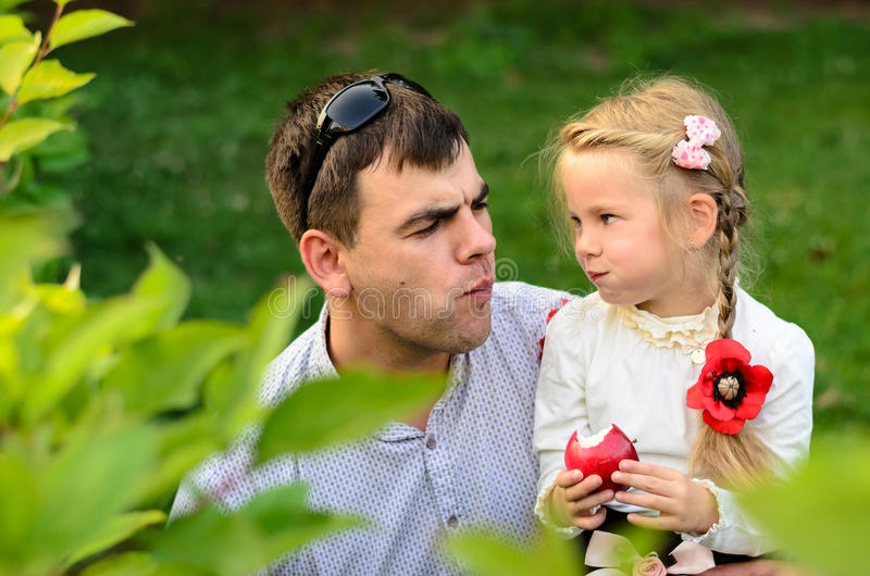 Father with daughter eating apples together. stock photo
