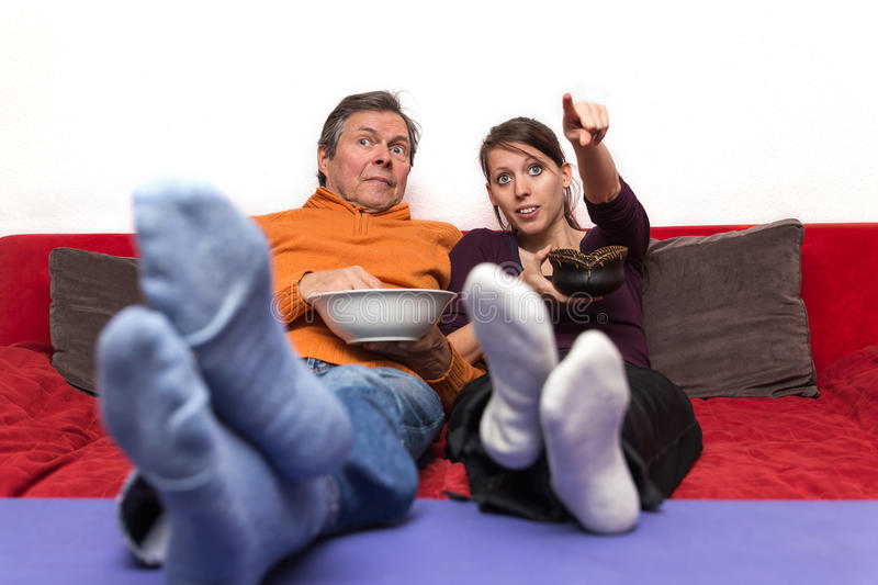 Father and daughter enjoys a movie. Father and daughter on a couch enjoys a movie stock photos