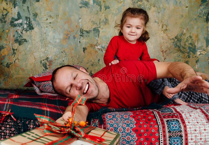 Father and daughter are fighting for a gift on the bed. A girl riding an adult tries to take a gift. stock photos