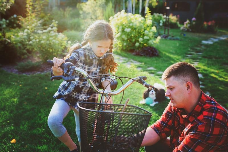 Father and daughter fixing problems with bicycle outdoor in summer. stock photos