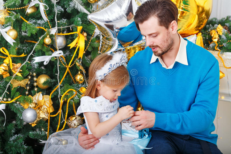 Father and daughter with gifts near a Christmas tree. royalty free stock photos