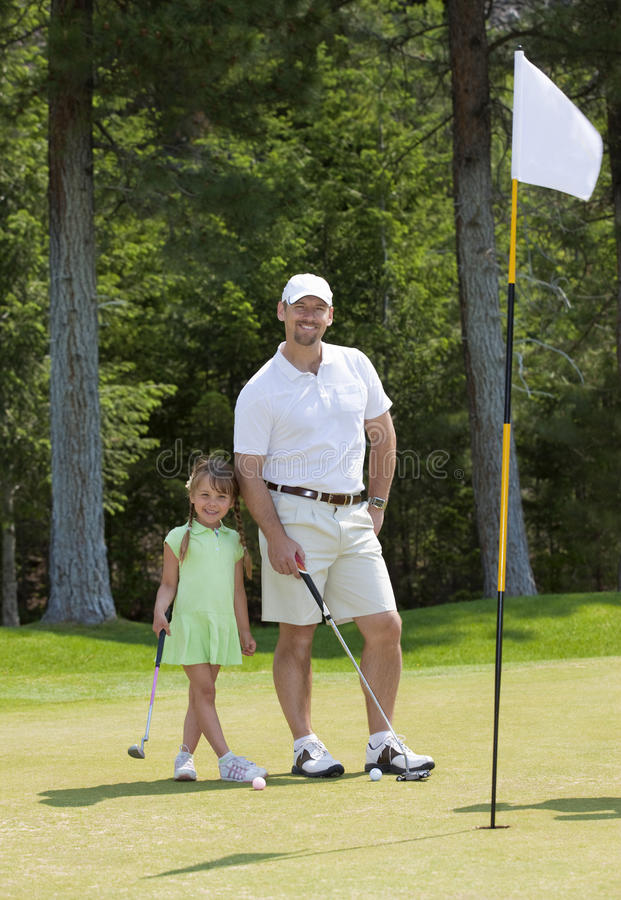 Father and Daughter Golfing. Full length view of father and young daughter standing on golf green stock photography