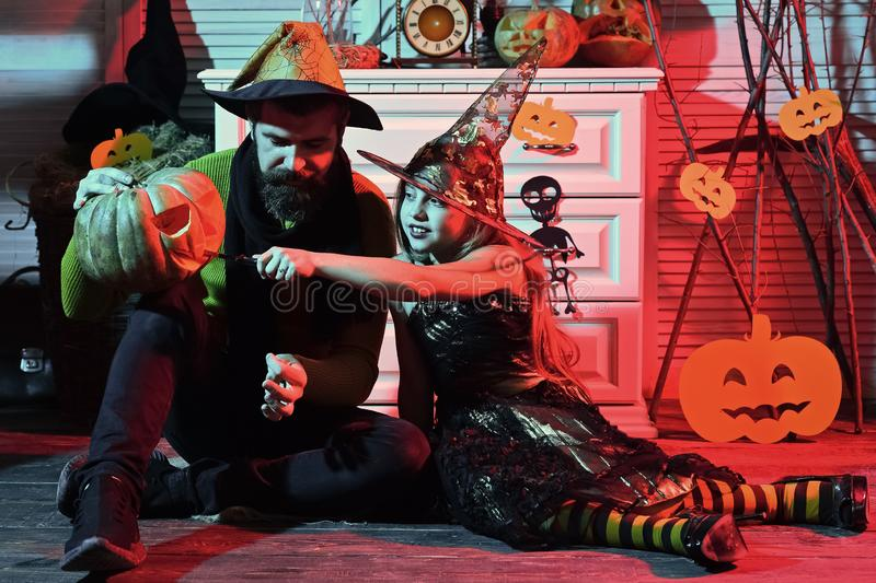 Father and daughter with Halloween decor. Wizard and little witch. In hats carve jack o lantern. Girl and bearded men with happy faces on red spooky carnival stock images