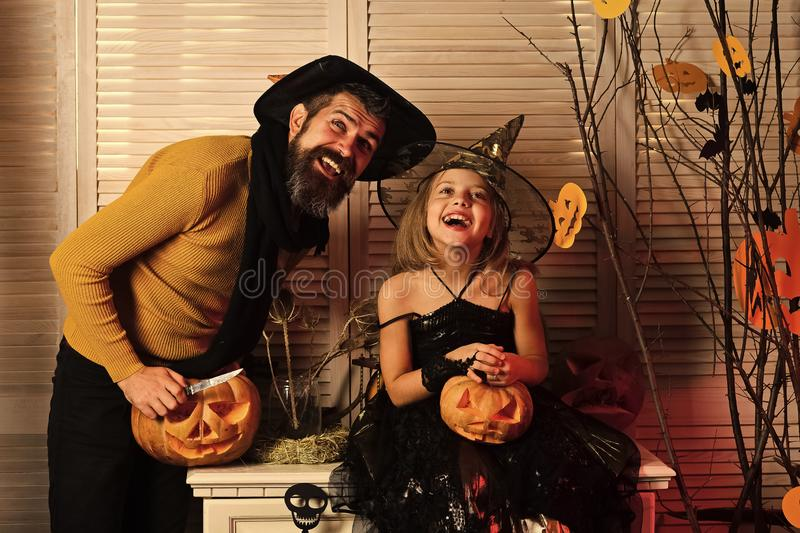 Father and daughter with Halloween decor. Wizard and little witch. In hats carve jack o lanterns. Halloween party concept. Girl and bearded men with excited royalty free stock photos
